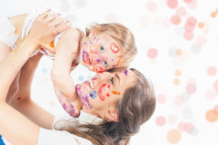 Happy mom and baby playing with painted face by paint Stock Photos