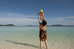 Happy mom with baby on tropical beach Stock Photo