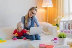 Mom babysitting and working on laptop. Happy mom babysitting and working on laptop Stock Photos