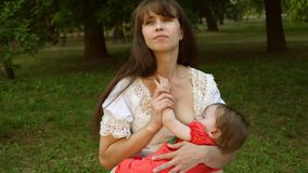 Happy mom breastfeeds a baby in the park la bench. Parental care during the first feeding of children. Walks in the open