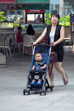 Happy mom Brings Child with stroller walks in park Stock Photo