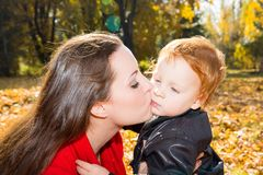 Happy mom and child boy hugging on nature. At fall stock images
