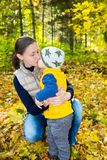 Happy mom and child boy hugging on nature at fall. Happy mom and child boy hugging on nature at faall. The concept of childhood and family. Beautiful Mother and Royalty Free Stock Photo