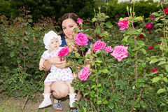 Happy mom and child girl hugging in flowers.  Beautiful Mother and her baby outdoors Stock Photo