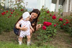 Happy mom and child girl hugging in flowers. Beautiful Mother and her baby outdoors Stock Photos