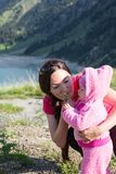 Happy mom and child girl hugging on nature The concept of childhood and family Royalty Free Stock Images