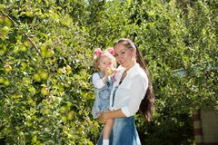 Happy mom and child girl hugging on nature The concept of childhood and family. Stock Photography