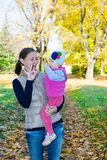 Happy mom and child girl hugging on nature at  fall. The concept of childhood and family. Royalty Free Stock Image