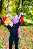 Happy mom and child girl hugging on nature at  fall. The concept of childhood and family. Stock Photos