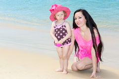 Happy mom and child girl hugging on tropical beach. Stock Images