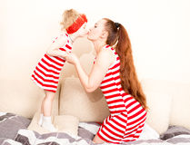 Happy mom and child girl kissing with love while looking at each other at home. Stock Images