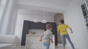 Happy mom with a child playing catch-up in the house in a bright apartment. Run around the house laughing and smiling