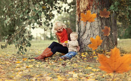 Happy mom and child playing and having fun together. Sitting under a tree on a warm autumn day, flying yellow maple leaves Royalty Free Stock Images