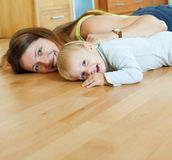 Happy mom and child on wooden floor. In home Stock Image