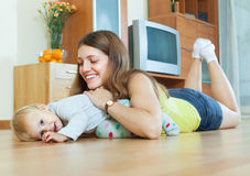 Happy mom with child on wooden floor Stock Images