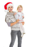Happy mom in Christmas hat and baby holding clock Stock Images