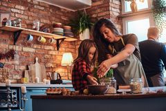 Happy mom cooking with her little daughter in loft style kitchen at morning. stock images