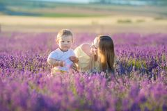 Happy mom with cute son on lavender background. Beautiful woman and boy in meadow field. Lavender landscape with lady and kid stock photos