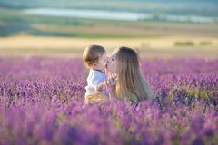 Happy mom with cute son on lavender background. Beautiful woman and boy in meadow field. Lavender landscape with lady and kid royalty free stock photos