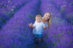 Happy mom with cute son on lavender background. Beautiful woman and boy in meadow field. Lavender landscape with lady and kid stock photo