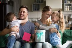 Happy mom and dad embracing kids thanking for gift boxes. Happy mom and dad embracing kids thanking son daughter for presenting gift boxes, excited smiling royalty free stock photo