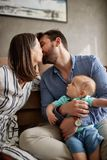Happy mom and dad holding their baby boy and kissing at home. Happy mom and dad holding their cute baby boy and kissing at home stock image