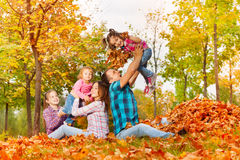 Happy mom and dad play with girls in autumn park Royalty Free Stock Images
