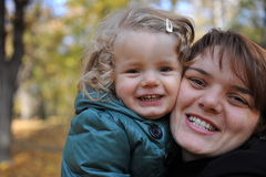 Happy mom and daughter. Portrait with happy mom and daughter in autumn park Stock Photo