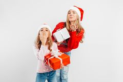Happy mom and daughter celebrate New Year, in Santa hats and sweaters with gifts in their hands, royalty free stock photos