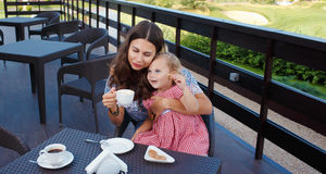 Happy mom and daughter eating ice cream. And drinking coffee outdoors. Family sitting at a table in the outdoor cafe and eating ice cream Royalty Free Stock Photography