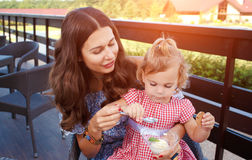 Happy mom and daughter eating ice cream. And drinking coffee outdoors. Family sitting at a table in the outdoor cafe and eating ice cream Stock Image