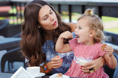 Happy mom and daughter eating ice cream Stock Images