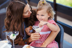 Happy mom and daughter eating ice cream. And drinking coffee outdoors. Family sitting at a table in the outdoor cafe and eating ice cream Royalty Free Stock Images
