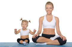 Happy mom and daughter engage in fitness on mat Royalty Free Stock Photos