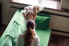 Happy mom and daughter enjoying pillow fight on sofa. Babysitter or nanny and little girl having fun together at home, mother with child playing on couch royalty free stock photo