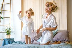 Happy mom and daughter having fun on the bed in dressing gowns royalty free stock photos