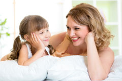 Happy mom and daughter lie on bed. Happy mom and child daughter lying on bed and looking each at other Stock Photography