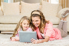 Happy mom and daughter lying on the floor. Using a tablet Royalty Free Stock Photo