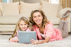 Happy mom and daughter lying on the floor. Using a tablet Stock Image
