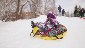 Happy mom and daughter sledding in winter in snow and playing snowballs. mother and child laugh and rejoice glide on an stock video