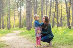 Happy mom and daughter talking with her daughter in the park stock images