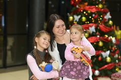 Happy mom with daughters at the Christmas tree with gifts royalty free stock photo