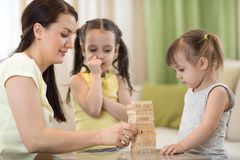 Happy mom and daughters at the table playing board game. Family mom and daughters at the table playing board game Royalty Free Stock Photos