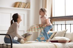 Happy mom and child girl enjoy pillow fight on bed. Happy mom elder sister and child girl enjoy funny pillow fight on bed, babysitter mother with little kid royalty free stock image