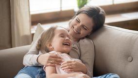 Happy mom embracing kid daughter laughing together lying on couch royalty free stock image