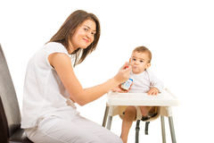 Happy mom feeding toddler boy with yogurt Stock Image