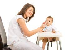 Happy mom feeding toddler boy with yogurt. Happy mom feeding her baby boy with yogurt isolated on white background Stock Image