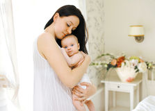 Happy mom gently hugs the baby. In a light room Royalty Free Stock Photos