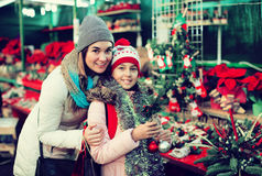 Happy mom and girl looking at flowers decoration royalty free stock photography
