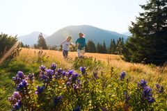 Happy mom and her teenage daughter are running. Around in a alpine meadow among lush green grass and blue wildflowers and having fun. Awesome travelling with Stock Images